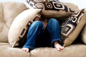 Chłopiec chowa się pod poduszkami