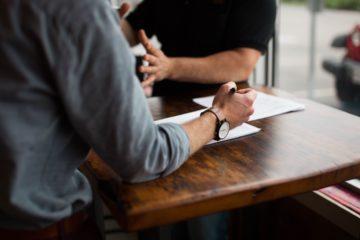 Ludzie dyskutują przy drewnianym stole