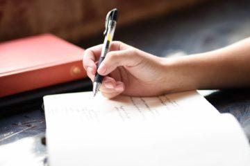 Kobieta pisząca w notatniku